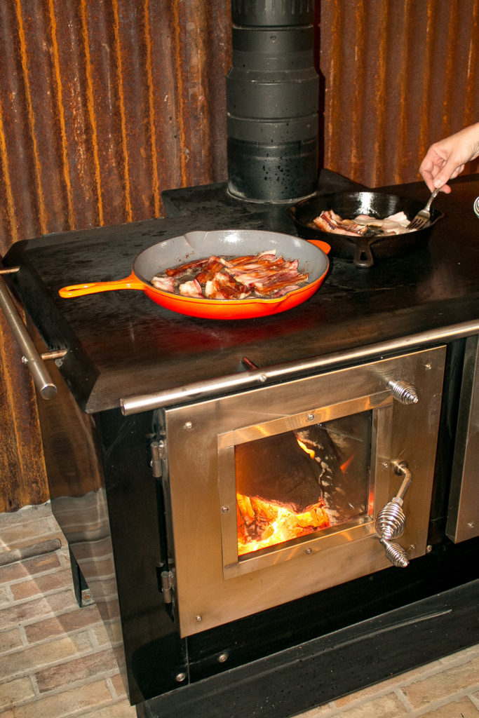 cooking bacon on a wood cookstove for a green Chile bacon quiche recipe