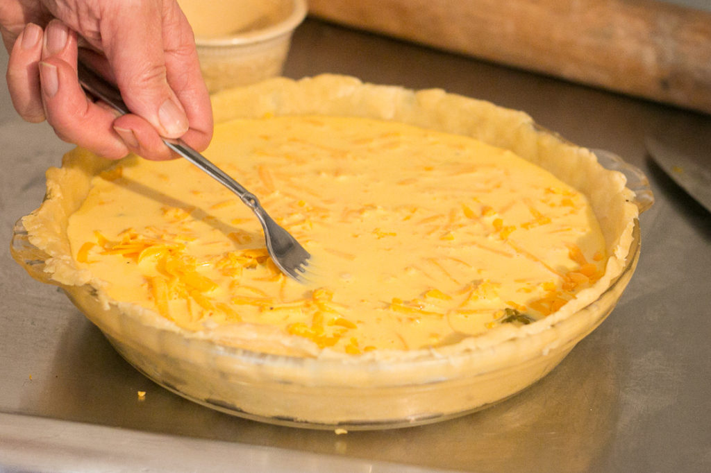 a hand holding a fork pressing the cheese below the egg mixture in the green Chile bacon quiche recipe