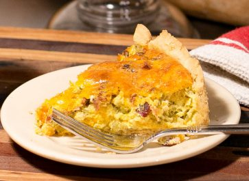 green Chile bacon quiche on plate with a fork